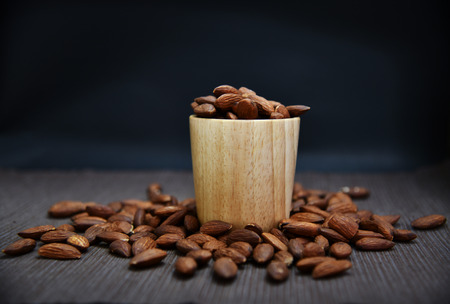 Roasted almonds in wooden cup and on napkin. Close up photo of Roasted Almonds.