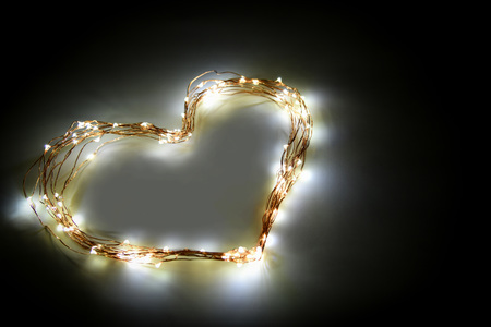 Heart shape made from twinkle lights on black background. Card design and decoration. Zdjęcie Seryjne