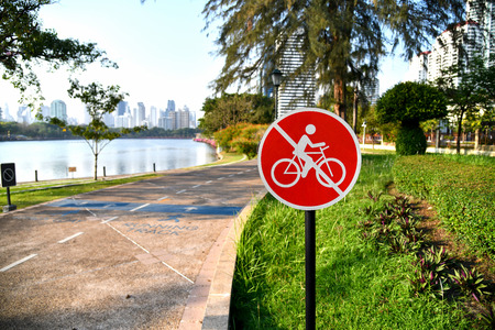 No bikes allowed sign beside running track at the park in Bangkok, Thailand with city, tree and lake view. Zdjęcie Seryjne