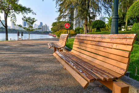Wooden bench, no bikes allowed sign and lamp post at the park in Bangkok, Thailand with lake, trees and city view.