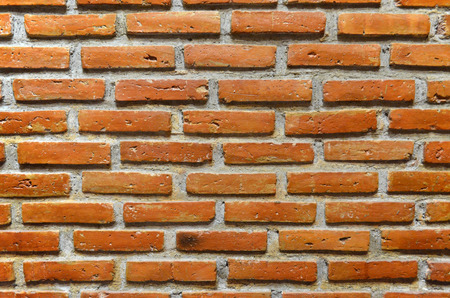 Orange and brown brick wall background texture and wallpaper. Exterior wall decoration and design.