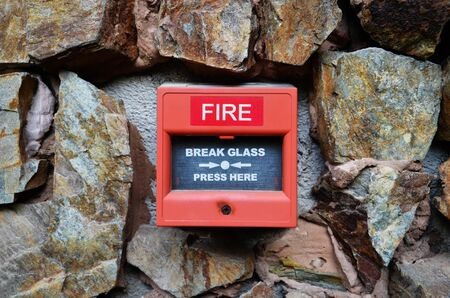 Close up of Fire alarm box on stone wall. Red Fire alarm press machine.
