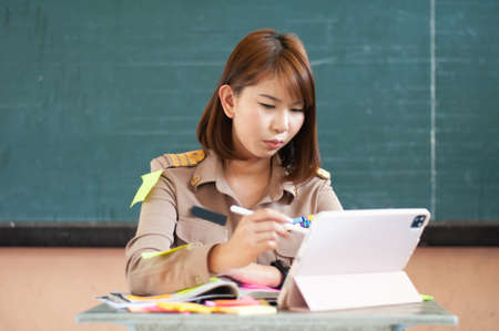 Female Thai teacher holding notebook to the computer while smiling Фото со стока