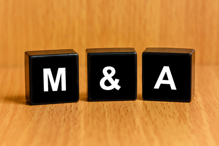 M&A or Merger and Acquisition text on black block