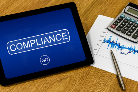 compliant: compliance word on digital tablet with calculator and financial graph