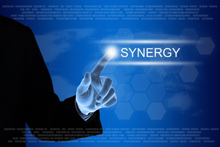concurrence: business hand pushing synergy button on a touch screen interface  Stock Photo