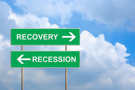 economic revival: recovery and recession on green road sign with blue sky