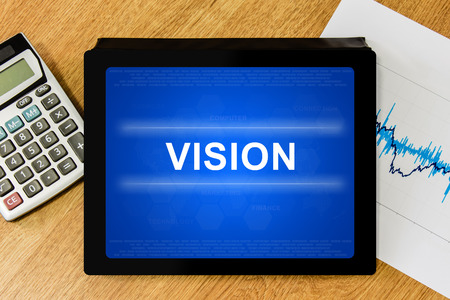 vision word on digital tablet with calculator and financial graph photo