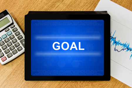 goal word on digital tablet with calculator and financial graph photo