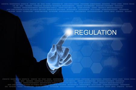 gobierno corporativo: mano de negocios que empuja el bot�n de regulaci�n en una interfaz de pantalla t�ctil