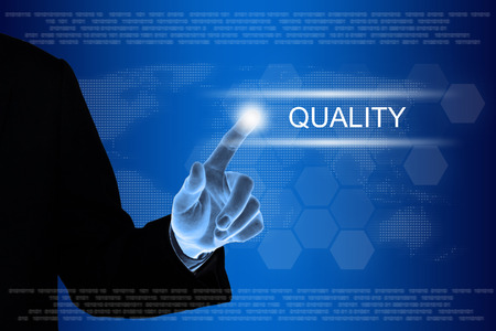 Quality Assurance: business hand pushing quality button on a touch screen interface