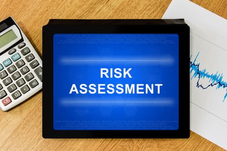 risky situation: risk assessment word on digital tablet with calculator and financial graph Stock Photo