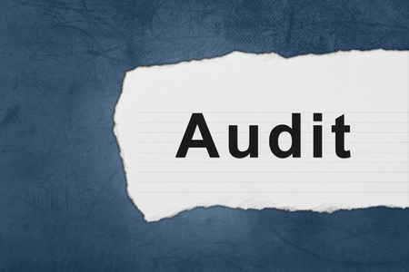 audit with white paper tears on blue texture photo