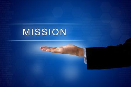 mision: bot�n de la misi�n con la mano sobre una interfaz de pantalla t�ctil