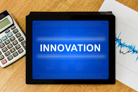innovation word on digital tablet with calculator and financial graph