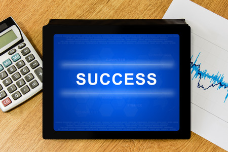 success word on digital tablet with calculator and financial graph photo