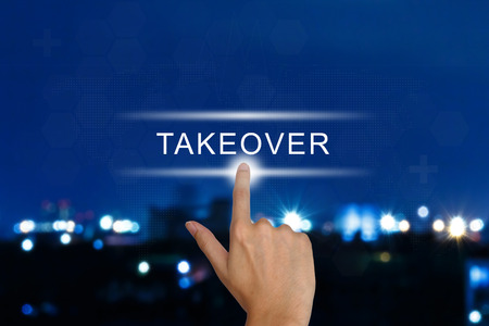takeover: hand clicking acquisition takeover button on a touch screen interface Stock Photo