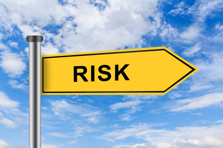 risk words on yellow road sign on blue sky photo