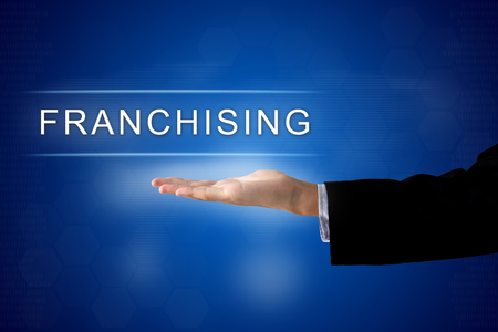 franchising: franchising button with business hand on a touch screen interface Stock Photo