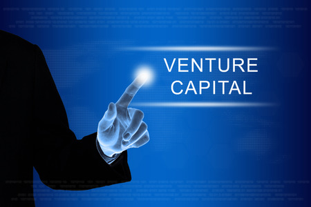 company ownership: business hand pushing venture capital button on a touch screen interface