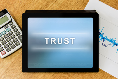 trust word on digital tablet with calculator and financial graph photo