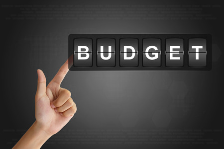 deficit target: hand clicking financial budget on Flip Board Display