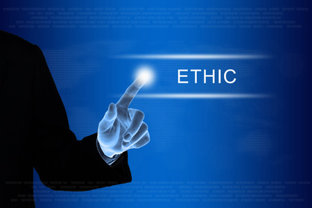 ethic: business hand pushing ethic button on a touch screen interface Stock Photo