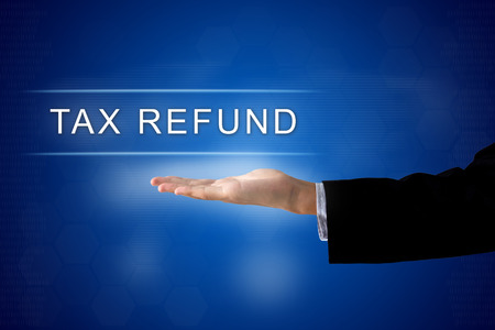 federal tax return: Tax refund button with business hand on a touch screen interface
