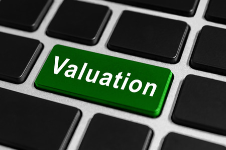 valuation green button on keyboard, business concept photo