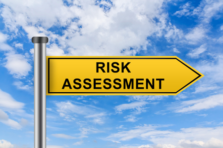 risk assessment words on yellow road sign on blue sky