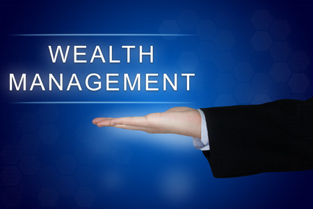 wealth management button with business hand on blue background Stock Photo
