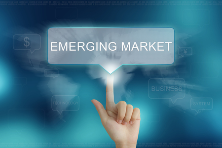 emerging markets: hand pushing on emerging market balloon text button