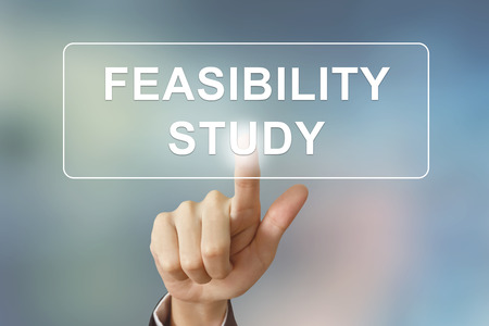 business hand pushing feasibility study button on blurred background