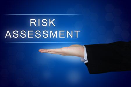 파란색 배경에 비즈니스 손으로 위험 평가 버튼