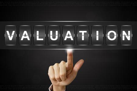 business hand pushing Valuation on Flipboard Display