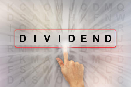 dividend: hand clicking dividend on word search puzzle Stock Photo