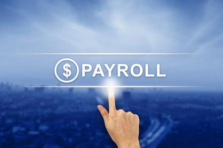 hand pushing payroll button on a virtual screen interface