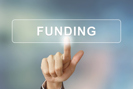 business hand pushing funding button on blurred background