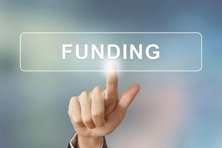 main d'affaires appuyant sur le bouton de financement sur fond flou