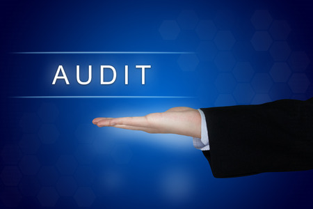 financial audit: audit button with business hand on blue background Stock Photo