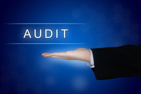 auditor�a: bot�n de auditor�a con la mano de negocios en fondo azul Foto de archivo