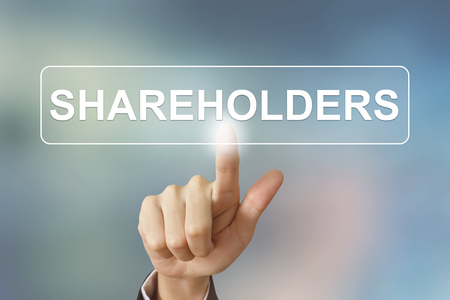 shareholders: business hand pushing shareholders button on blurred background Stock Photo