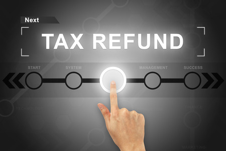federal tax return: hand clicking tax refund button on a touch screen