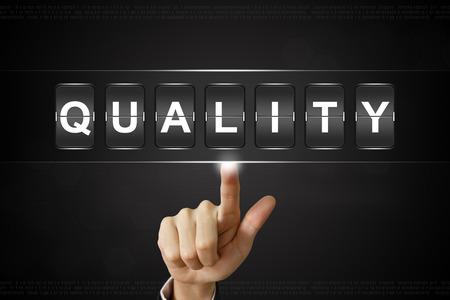 business hand pushing quality on Flipboard Display
