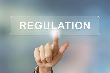 control de calidad: mano de negocios empujando el botón reglamento sobre fondo borroso
