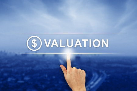 valuation: hand pushing financial valuation button on a virtual screen interface Stock Photo