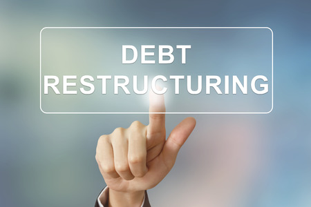 creditors: business hand pushing debt restructuring button on blurred background