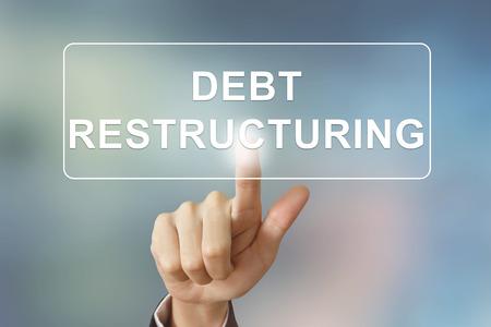 main d'affaires appuyant sur le bouton de restructuration de la dette sur fond flou