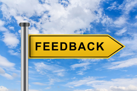 feedback words on yellow road sign on blue sky Stock Photo