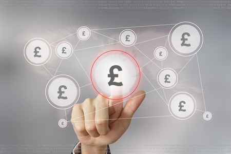 currency symbol: hand pushing british pound currency button with global networking concept Stock Photo